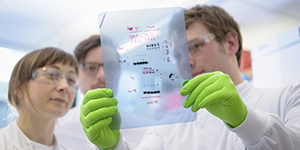 3 scientists in white lab coats looking at a Western blot X-ray film
