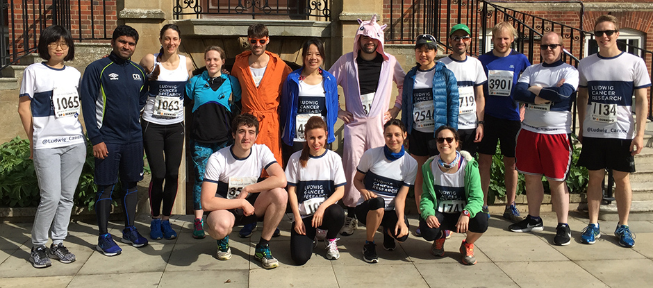 Ludwig Oxford runners posing for a photo taken before the Town and Gown race in front of the steps of the Dunn School of Pathology, with one person in a dragon fancy dress costume