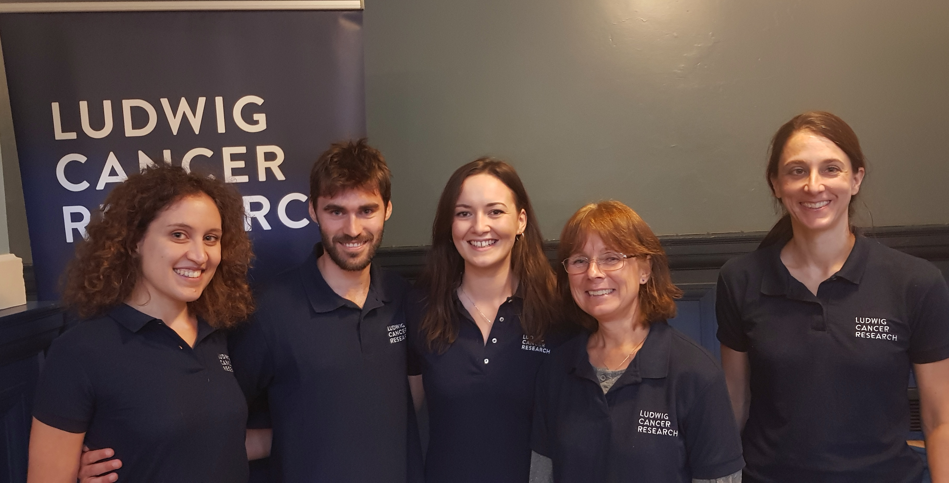 5 Ludwig Oxford volunteers posing in front of the Ludwig Cancer Research banner at the IF Oxford event 2018